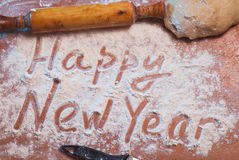 happy-new-year-written-flour-christmas-background-preparing-food-rolling-pin-knife-wooden-table-80731084